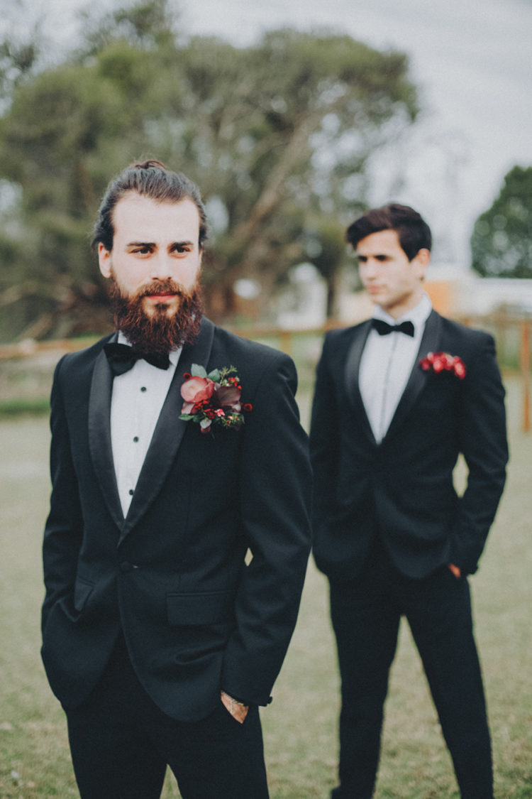 a classic black tux with a white shirt with black buttons and a bold redand burgundy boutonniere