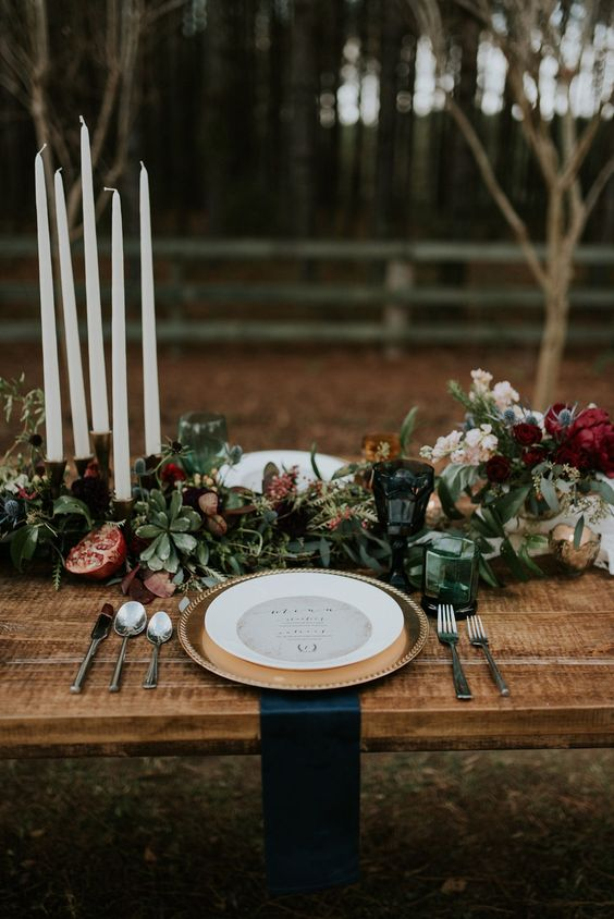 a lush moody table setting with a table runner with blooms, succulents and pomegranates, gilded touches and teal napkins
