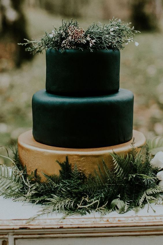 a moody Halloween wedding cake with a gilded tier and black ones, topped with greenery