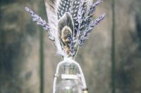 16 a simple wedding centerpiece of a bottle, lavender and some feathers plus beads