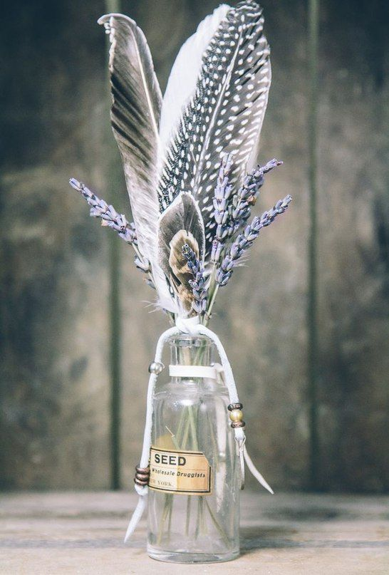 a simple wedding centerpiece of a bottle, lavender and some feathers plus beads