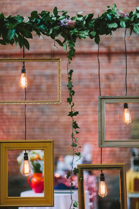 wedding decor with fresh greenery, frames and bulbs hanging down