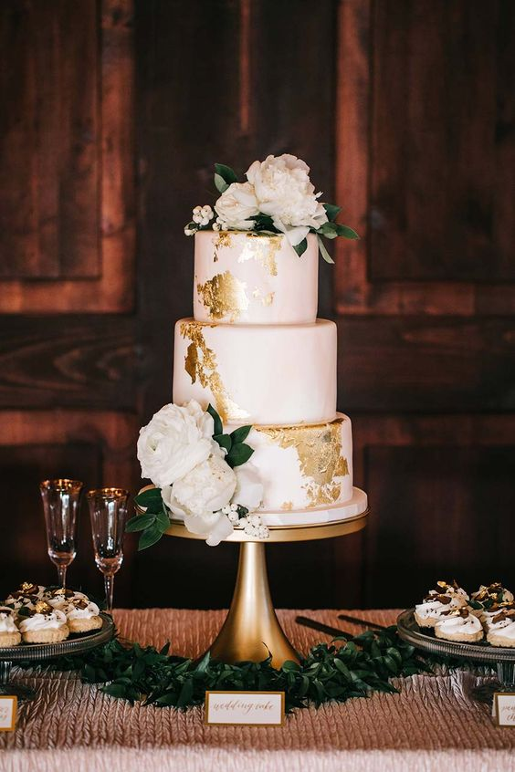a blush wedding cake with gold foil and white blooms on top looks very cute and chic