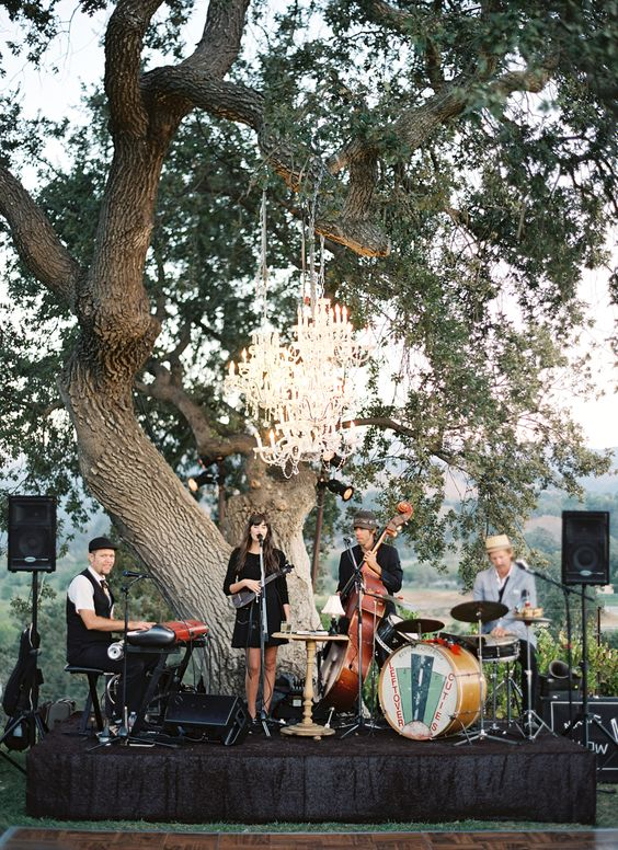 a cool wedding band playing outdoors on a separate podium accented with a glam chandelier
