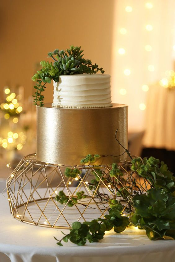 a creative geometric wire cake stand accents the cake and additional lights help with that