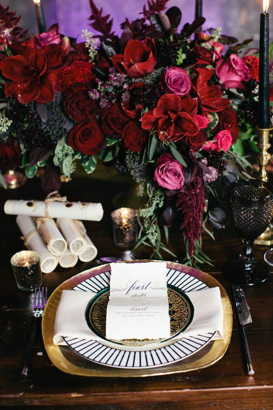 a luxurious moody table setting with a lush floral centerpiece, black candles and glasses and gilded touches