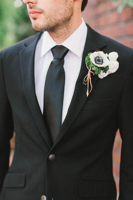 a modern Halloween groom's look done with a blakc suit, tie, a white shirt and a white anemone boutonniere