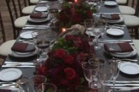 17 a moody tablescape with a black tablecloth, black menus, burgundy napkins and floral centerpieces