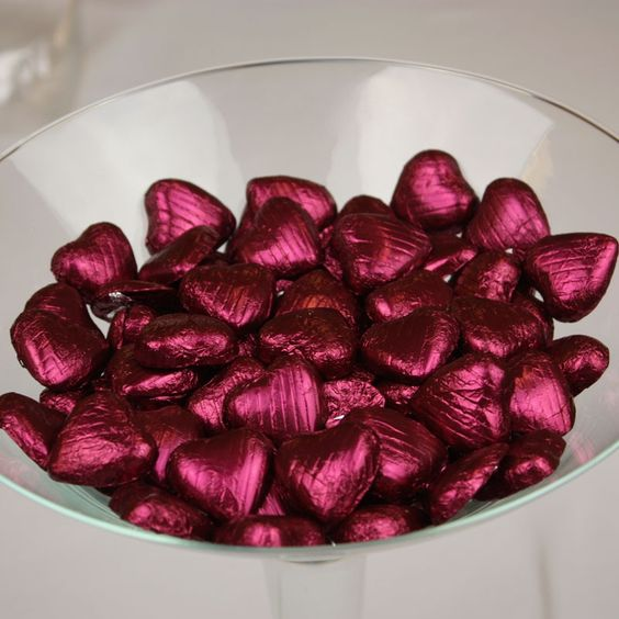 mini heart chocolate candies wrapped in burgundy foil are a budget friendly idea