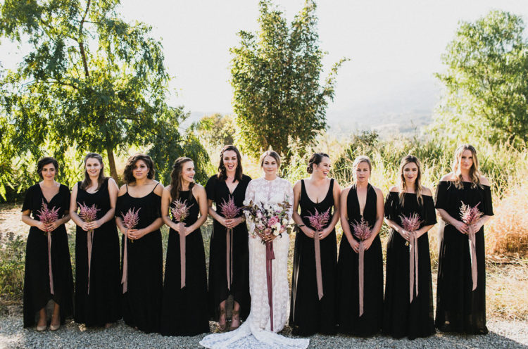 mismatching black bridesmaids' maxi dresses plus pink bouquets look very chic
