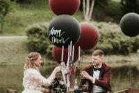 18 a black, burgundy and grey wedding reception space with florals, large balloons and candles