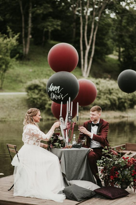 a black, burgundy and grey wedding reception space with florals, large balloons and candles