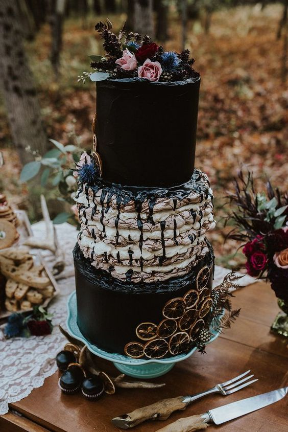 a crazy Halloween wedding cake in black and with a part of Icelandic wedding cake, decorated  with citrus, thistles and blooms