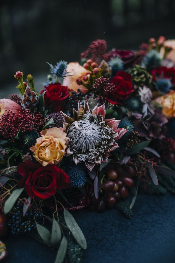 a gorgeous moody wedding centerpiece with thistles, berries, grapes and red and orange blooms plus king proteas