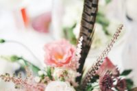 18 a textural wedding centerpiece with pink, mauve and blush blooms and feathers