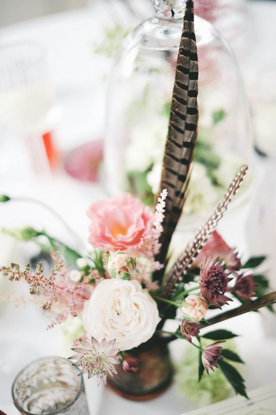 a textural wedding centerpiece with pink, mauve and blush blooms and feathers