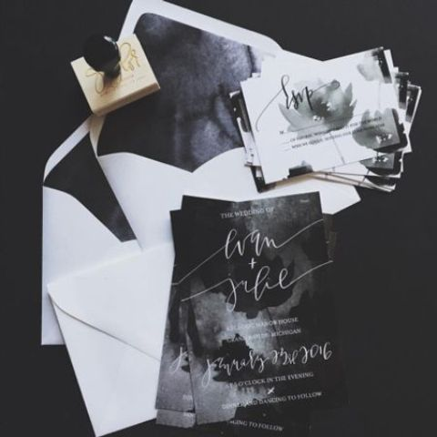a black, white and grey watercolor wedding invitation suite with white envelopes and moody invites