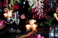 19 a burgundy and black tablescape with hanging florals and candles for a luxurious wedding