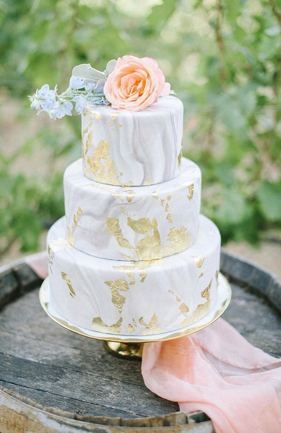 a chic grey marble wedding cake with gold foil and a peachy bloom on top