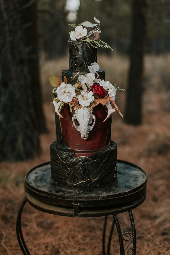 a statement Halloween wedding cake in black and burgundy, with touches of gold, a skull and lush blooms