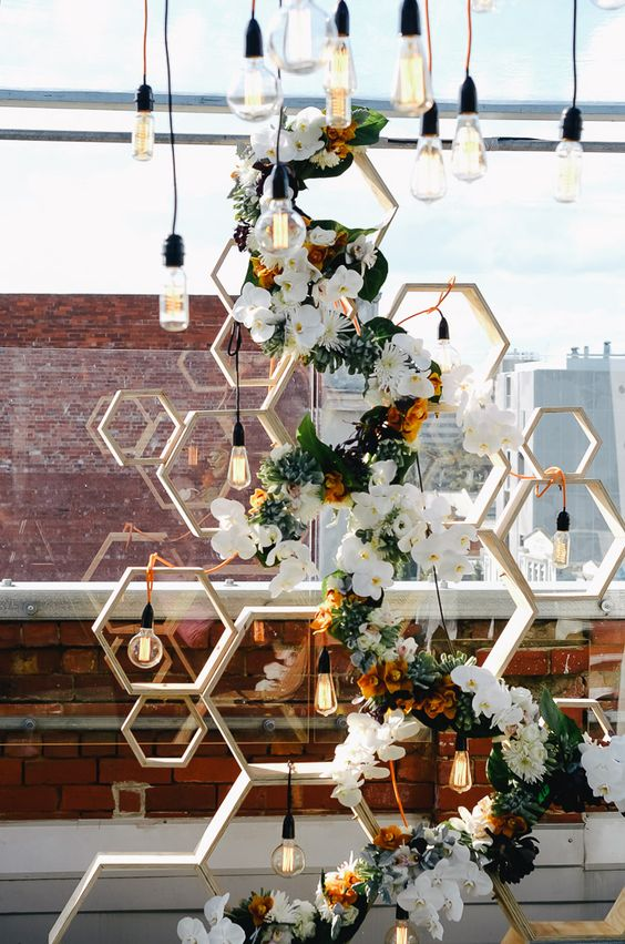 a bold modern wedding backdrop of hexagons, lush blooms and Edison bulbs all over