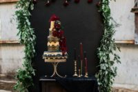 20 a cake backdrop with a chalkboard wall covered with greenery, black fabric and black and burgundy candles
