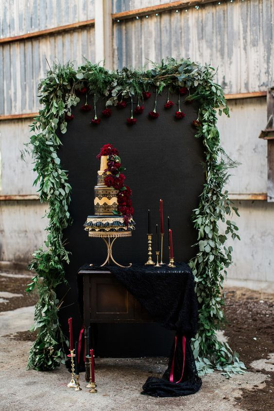 a cake backdrop with a chalkboard wall covered with greenery, black fabric and black and burgundy candles
