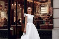 20 a modern midi wedding dress with ruffled cap sleeves and a full skirt plus nude heeled sandals