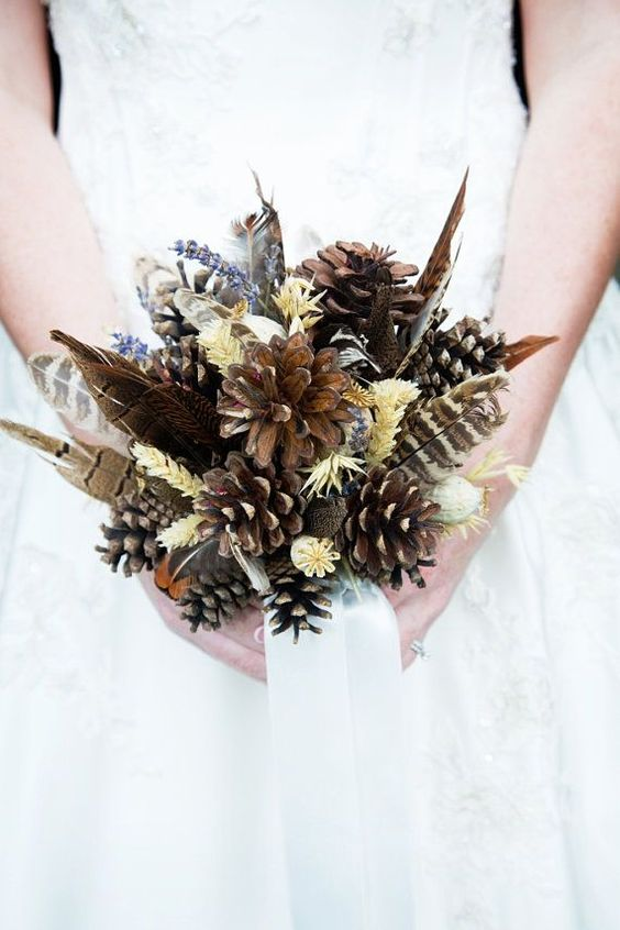 a fall boho wedding bouquet with feathers, pinecones, herbs and an airy ribbon