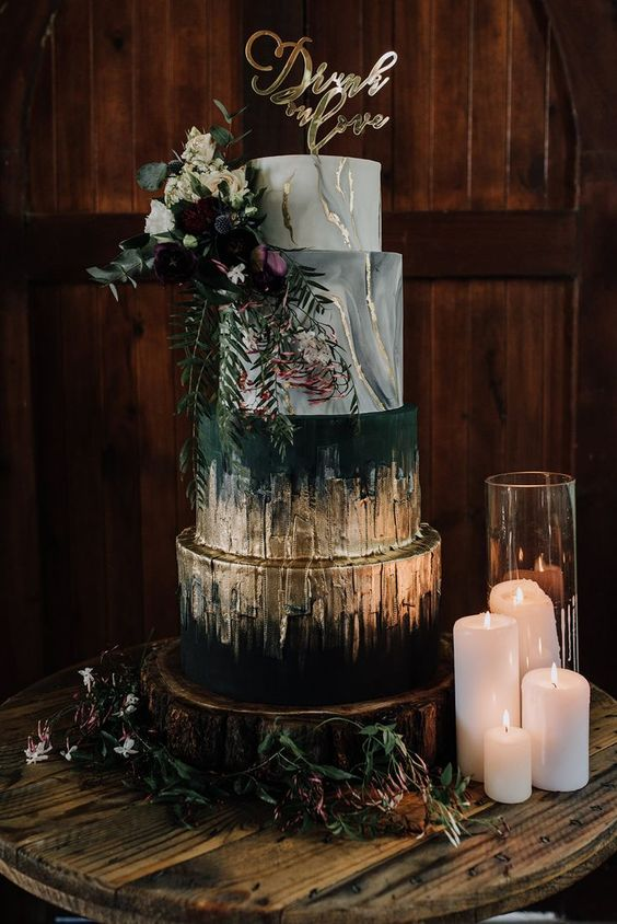 a jaw-dropping wedding cake with marble and black layers and much gold foil plus moody blooms