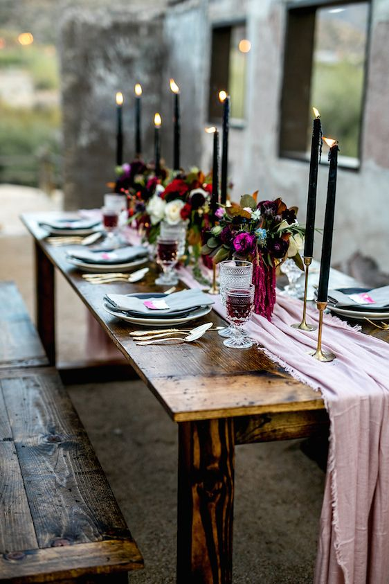 a moody decadent wedding table setting with a pink table runner, black candles, lush dark florals