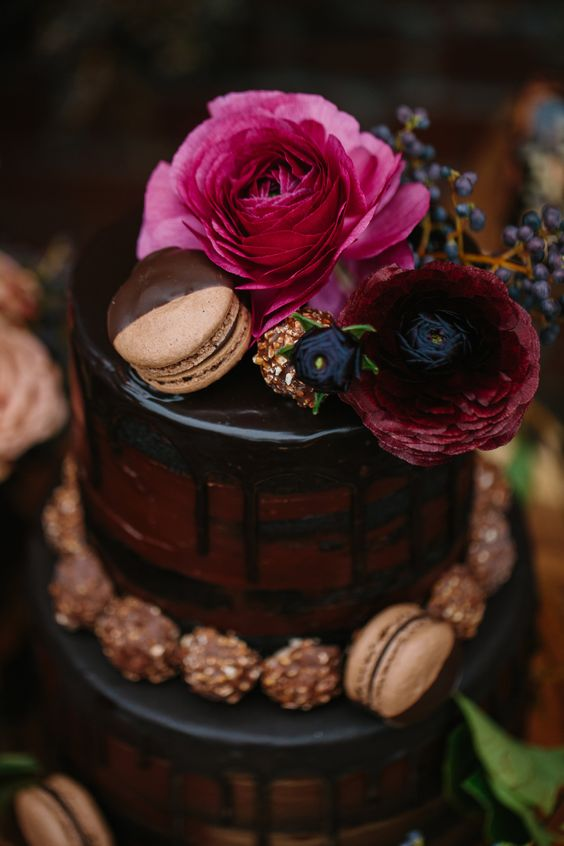 a chic moody red velvet wedding cake with chocolate drip, lined up with chocolatecandies and topped with a macaron and blooms