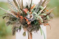 22 a fall boho wedding bouquet with greenery, feathers and orange blooms plus long ribbons