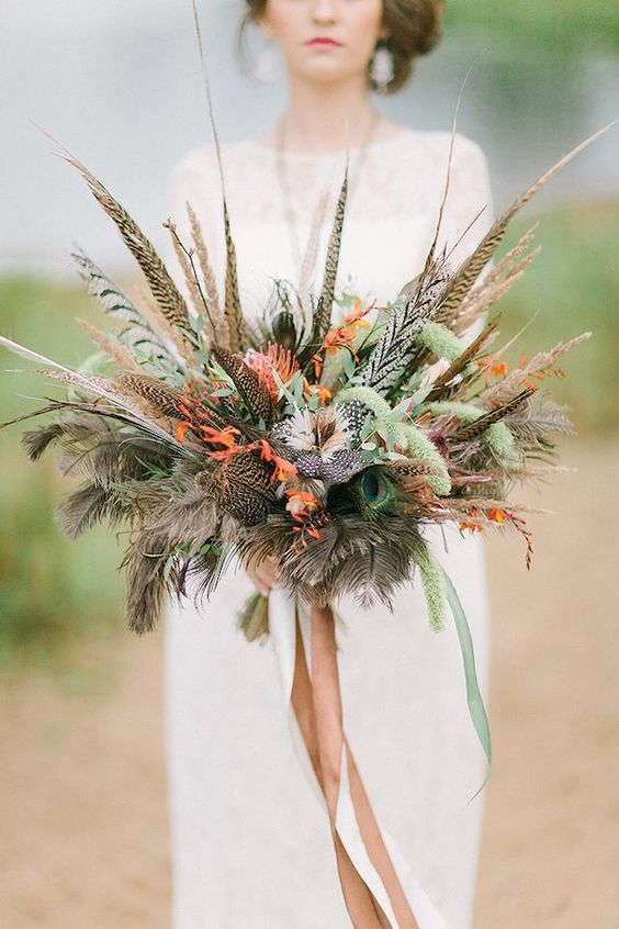 a fall boho wedding bouquet with greenery, feathers and orange blooms plus long ribbons
