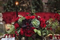 22 a moody Halloween centerpiece with red roses, greenery, dark foliage and cabbage plus a moss table cover