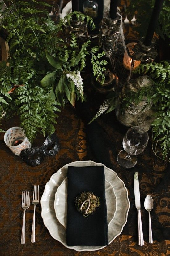 a moody Halloween tablescape with lush greenery, black candles and napkins, white porcelain and silver
