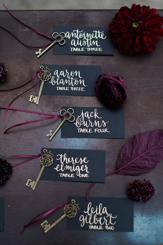black and gold escort cards with vintage keys and burgundy blooms and leaves for a bold touch