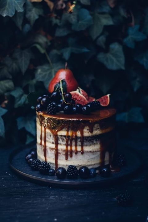 a decadent Halloween semi-naked wedding cake with caramel drip and berries and fruits on the top