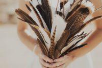 23 a feather and branch wedding bouquet is a creative boho wedding idea