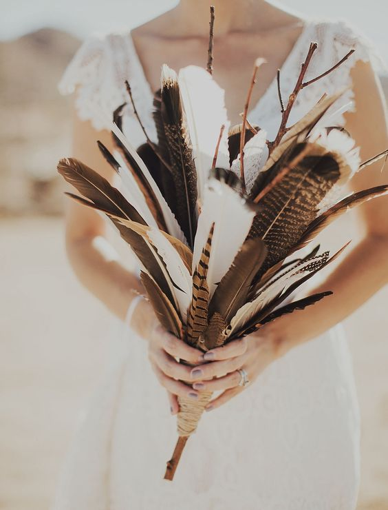 a feather and branch wedding bouquet is a creative boho wedding idea