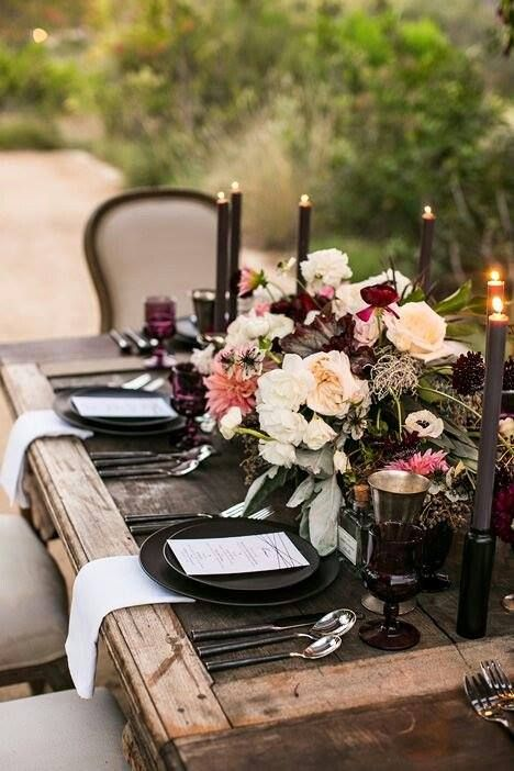 a moody haunted wedding tablescape with an uncovered table with a moody floral centerpiece, black candles and chargers and colored glasses