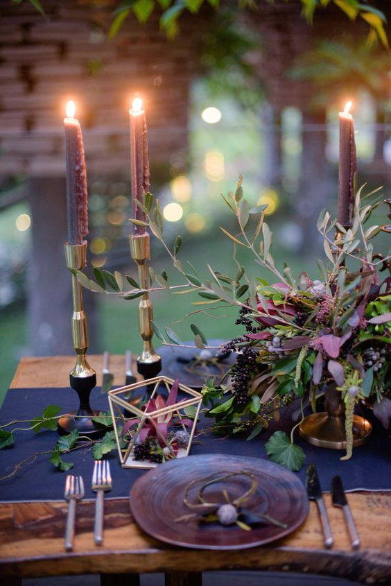 a moody tablescape with a unique centerpiece with greenery, foliage in different shades and berries plus dusty pink candles
