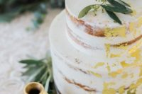 23 a naked wedding cake with gold foil and some eucalyptus for a rustic wedding