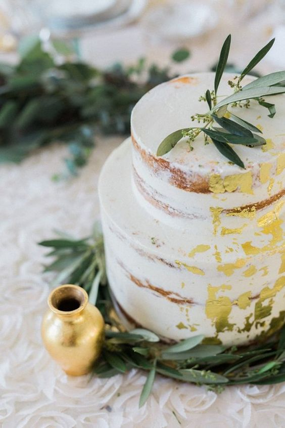 a naked wedding cake with gold foil and some eucalyptus for a rustic wedding