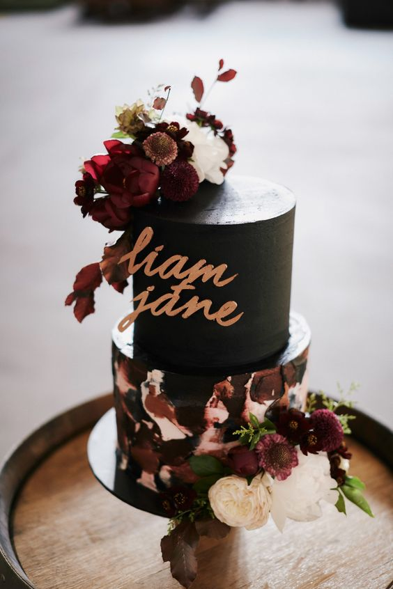 a gorgeous wedding cake with a black tier and a textural white and burgundy one plus white and burgundy blooms