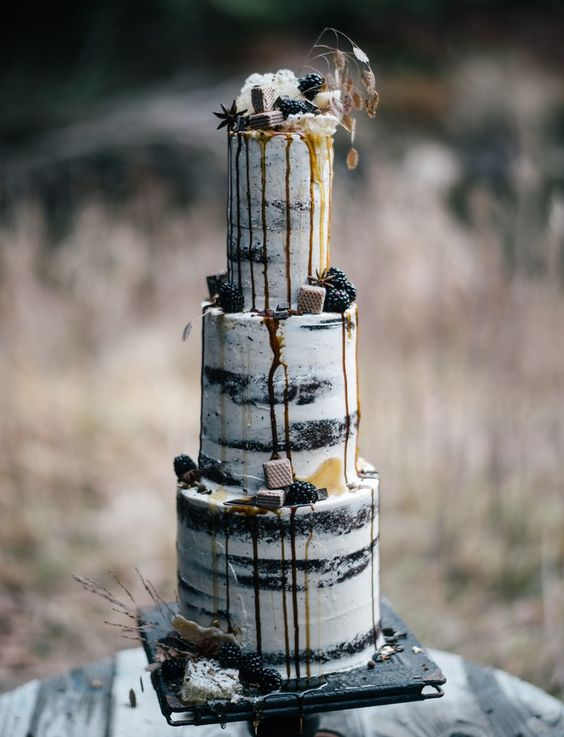a moody semi-naked wedding cake with caramel drip, topped with berries and waffles