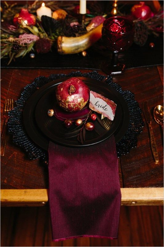 a place setting styled with a plum colored napkin, black chargers and plates, pomegranates and a colored glass