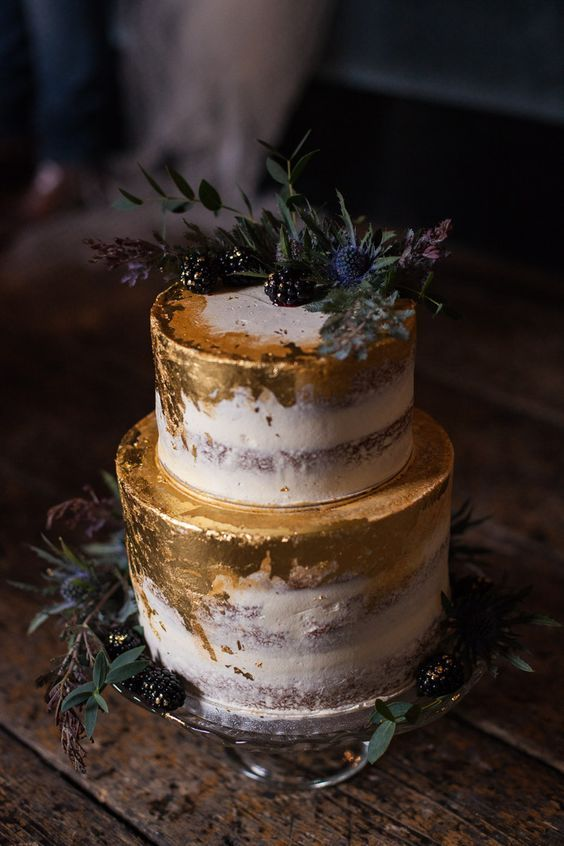 a semi naked wedding cake with gold foil, blackberries and thistles for a fall wedding