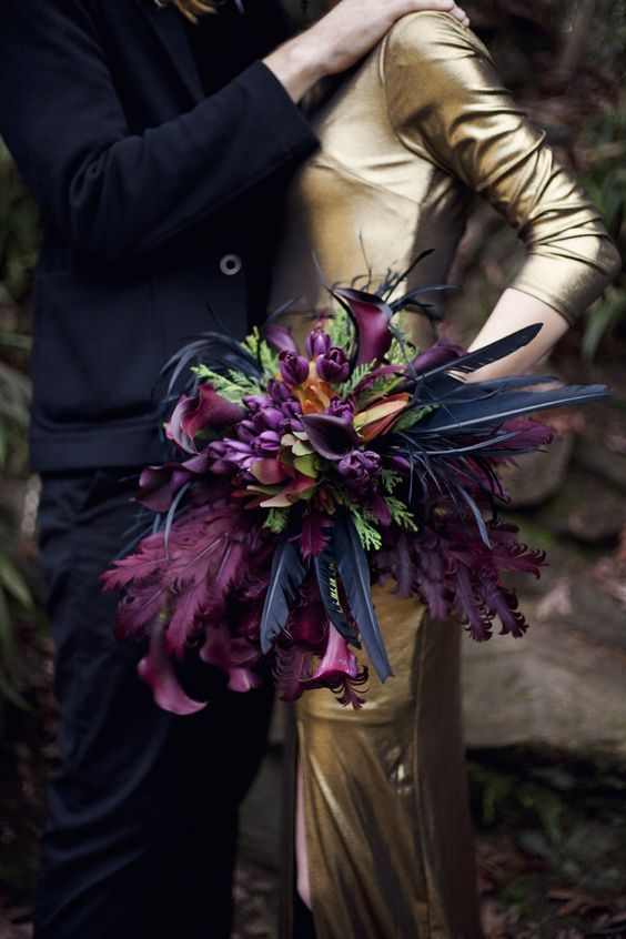 a super bold wedding bouquet with fuchsia and black feathers for a dramatic touch