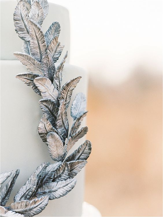 a light blue wedding cake decorated with feathers is a gorgeous ethereal idea